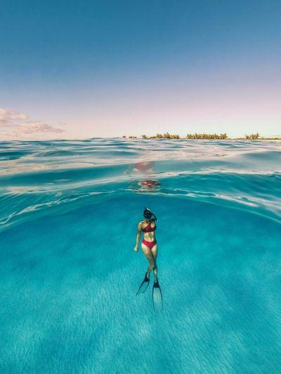 Man surfing in sea against blue sky