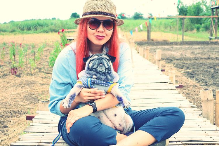 Portrait of woman with dog sitting on footbridge at agricultural field
