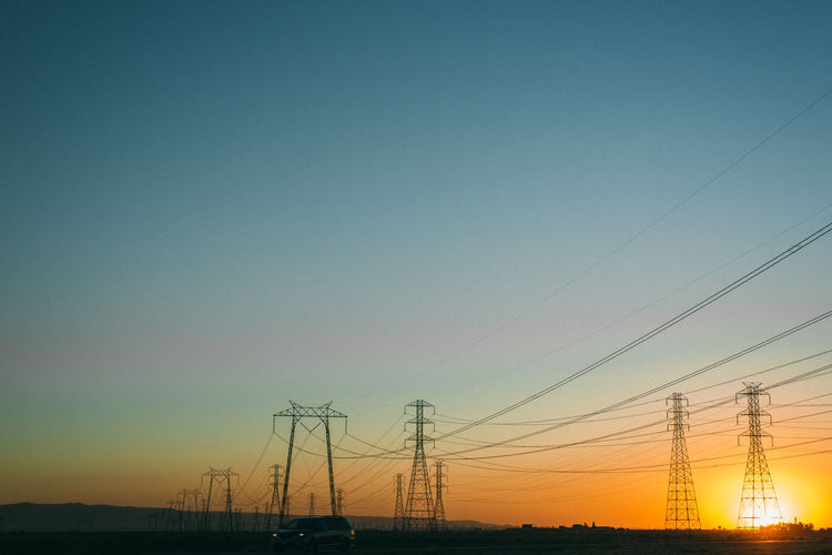 Electricity pylon against clear sky during sunset