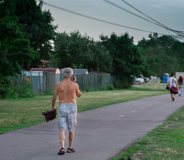 Day Full Length Growth Incidental People Leisure Activity Lifestyles Males  Men Nature People Plant Real People Rear View Road Shirtless Shorts Street Transportation Tree Walking Summer Road Tripping
