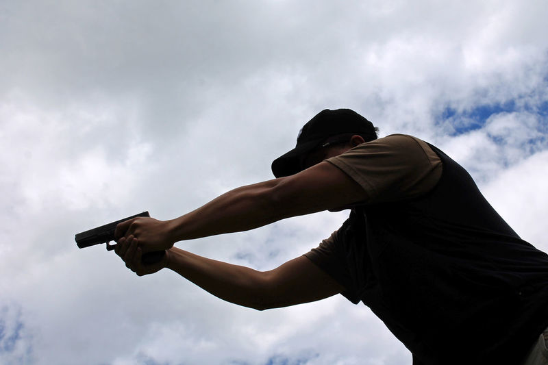 Low Angle View Of Man Shooting Gun Against Sky