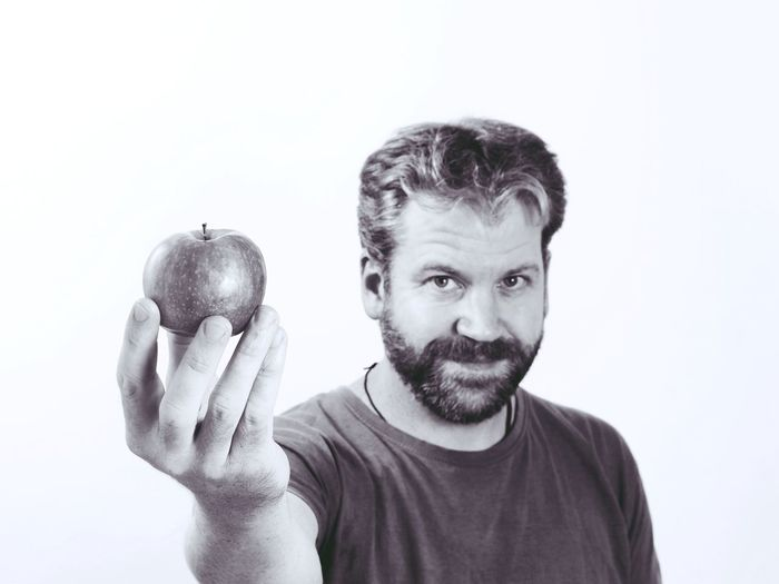 Portrait of man with apple against white background
