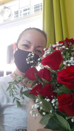 Portrait of woman with red flowers at home
