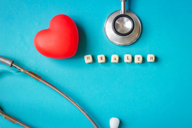 Directly above shot of heart shape with text blocks and stethoscope on blue background