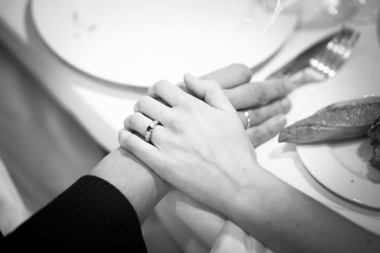 Close-up high angle view of wife touching husband hand at dining table