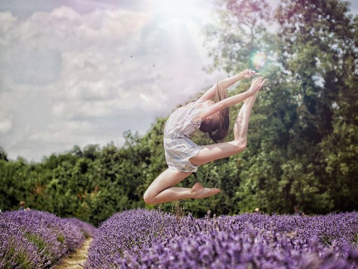 Woman Jumping On Lavender Field Against Sky