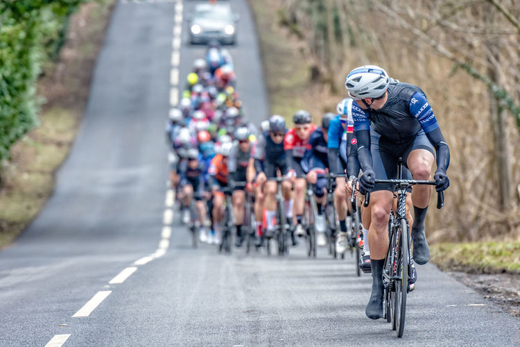 Local UK road race of elite cyclists racing a spring classic cycle race in Kent Fashion Green Hubs LINE Road TEAMS Trees Bicycles Bike Race Blue Bunch Canyon Car Cyclists Grears Handlebar Hats Markings Pedal Peleton Spokesman Spring Tyres Wheels Whilelines