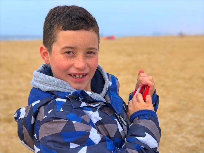Close-Up Portrait Of Boy Smiling While Standing At Beach During Winter