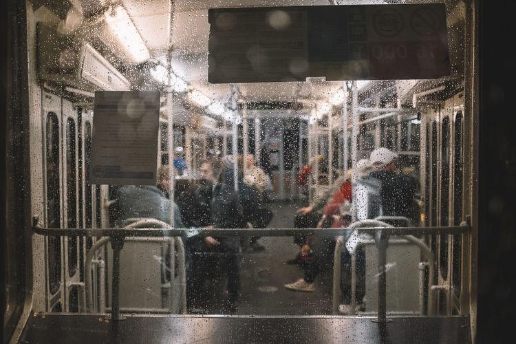 People walking on wet glass window in city