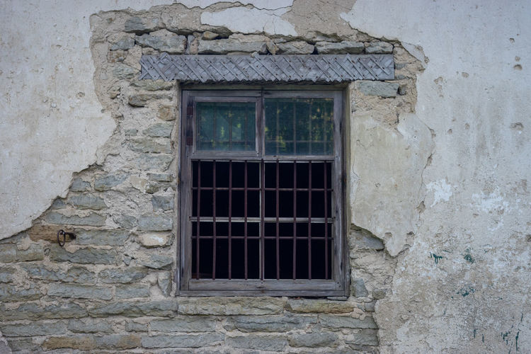 Window Architecture Built Structure Building Wall - Building Feature Building Exterior Old Day No People Outdoors Wall House Security Protection Safety Weathered Security Bar Closed Grid Low Angle View Stone Wall Window Frame Decay Structure Lines Behind Bars Broken Window Decaying Building Heritage Protection Limestone Walls Old Wall