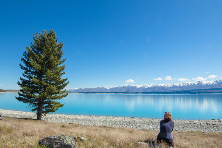 Woman sitting at lakeshore against blue sky
