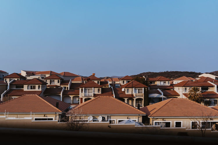 Houses in city against clear blue sky