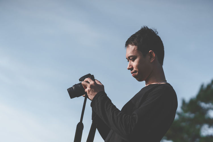 Asian man photographer is looking his photo from camera. Portrait Nature Outdoors Feeling Sunlight Photographer Travel Traveler Tourism Happy Happiness Copy Space Young Men Sky Tan Camera Lifestyles Journey Hobby Amaturephotography Vacations Leisure Looking Freedom Passion