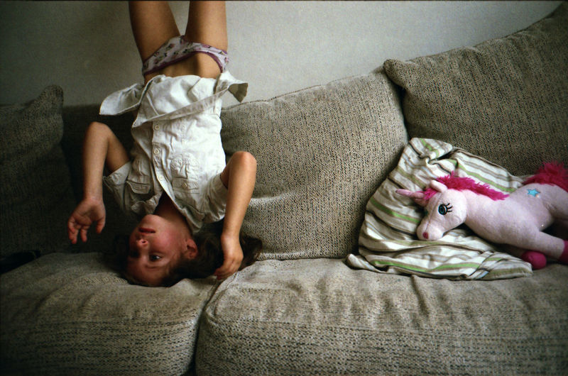 Girl practicing headstand on sofa at home