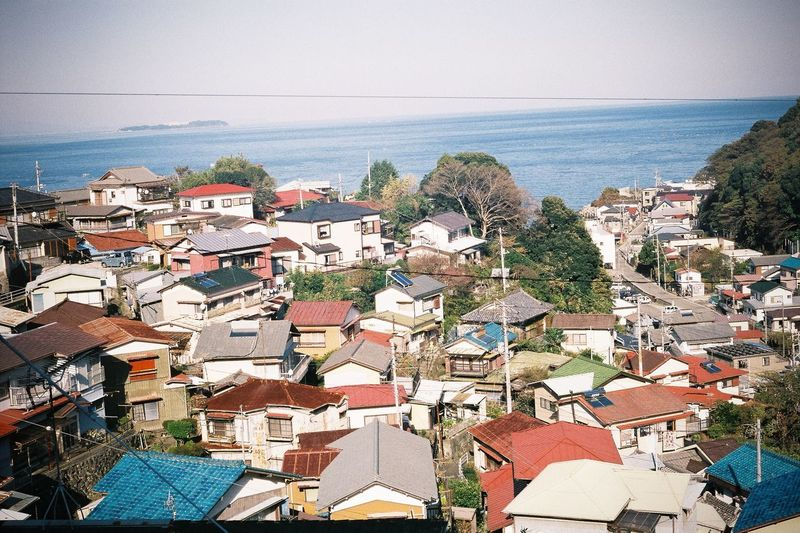 High angle view of houses by sea against sky