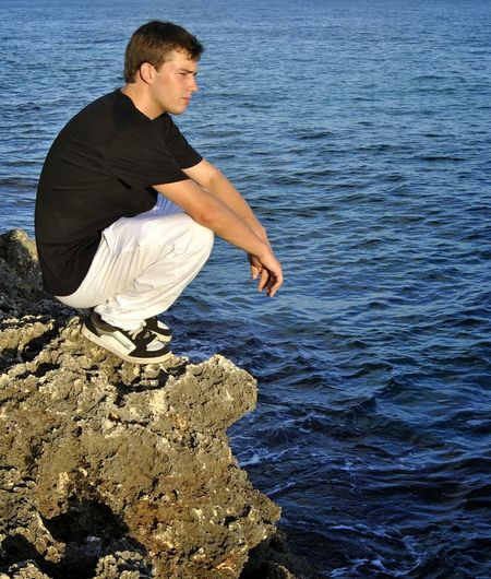 Side view of young man on rock in sea