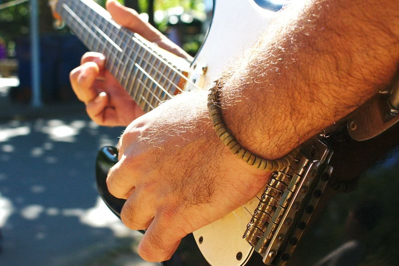 Cropped Hand Of Man Playing Guitar Outdoors