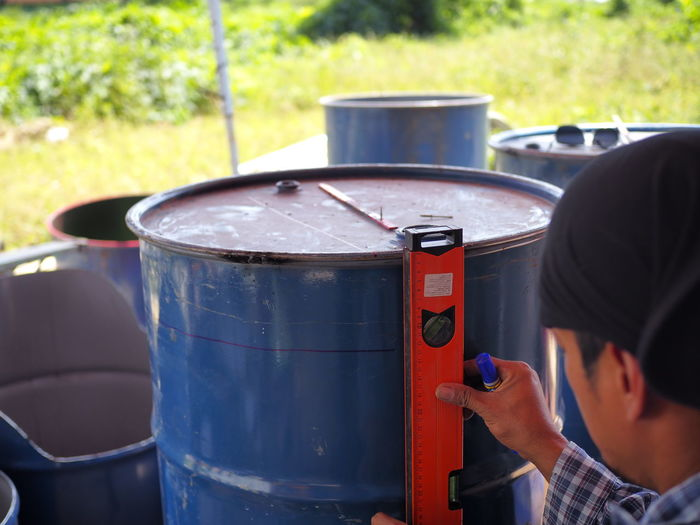 Close-Up Of Man Measuring Barrel