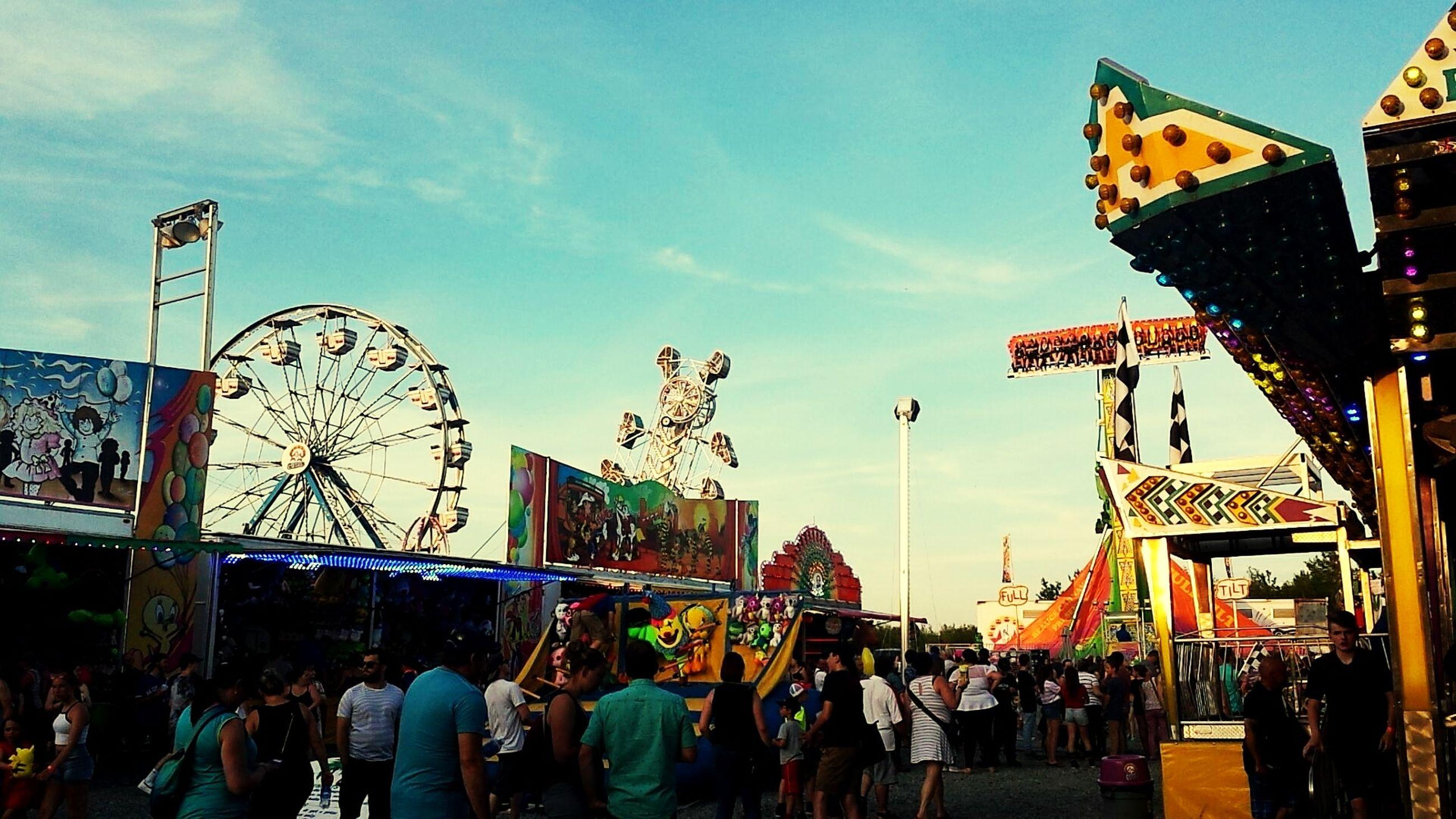 amusement park, arts culture and entertainment, amusement park ride, group of people, crowd, real people, sky, large group of people, leisure activity, ferris wheel, men, women, architecture, cloud - sky, enjoyment, lifestyles, day, adult, built structure, nature, outdoors, festival, fairground