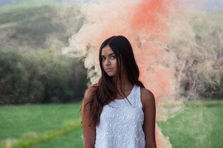 Young woman surrounded by pink smoke