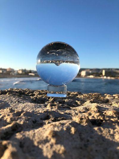 Close-up of crystal ball on beach against clear blue sky