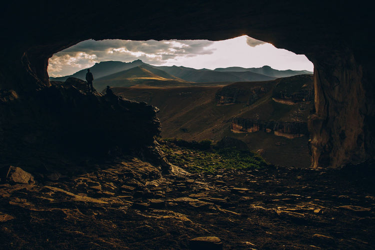 Man standing at cave against mountains during sunset