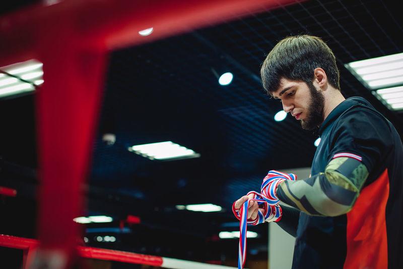 Side view of man wearing bondage in boxing ring