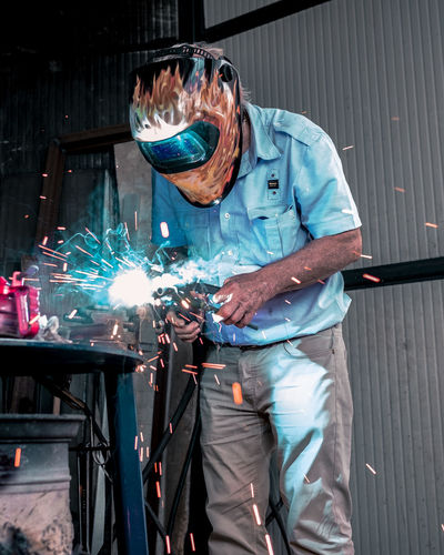 well dressed worker Adult Blurred Motion Holding Indoors  Industry Men Metal Metal Industry Occupation One Person Protection Protective Workwear Real People Safety Security Skill  Sparks Three Quarter Length Welder Welding Working