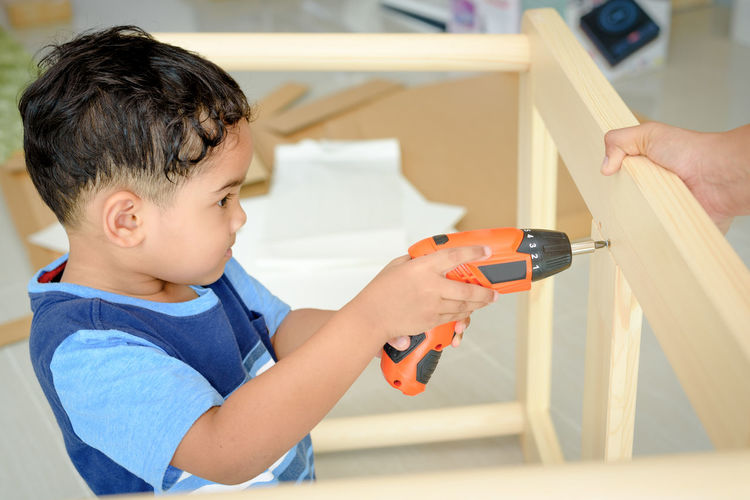 Boy drilling wood held by person at home