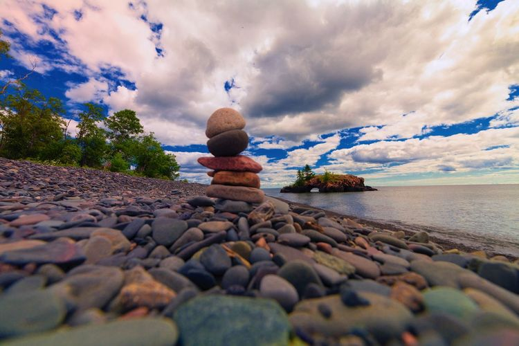Surface level view of stones stacked at seashore against cloudy sky