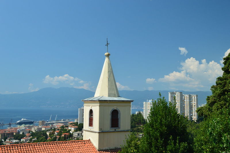 Panoramic view of buildings and trees against sky