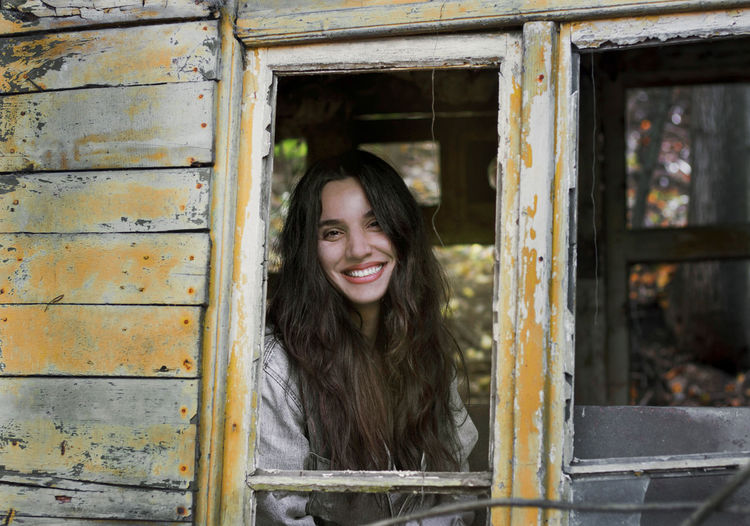 Portrait of smiling young woman against window