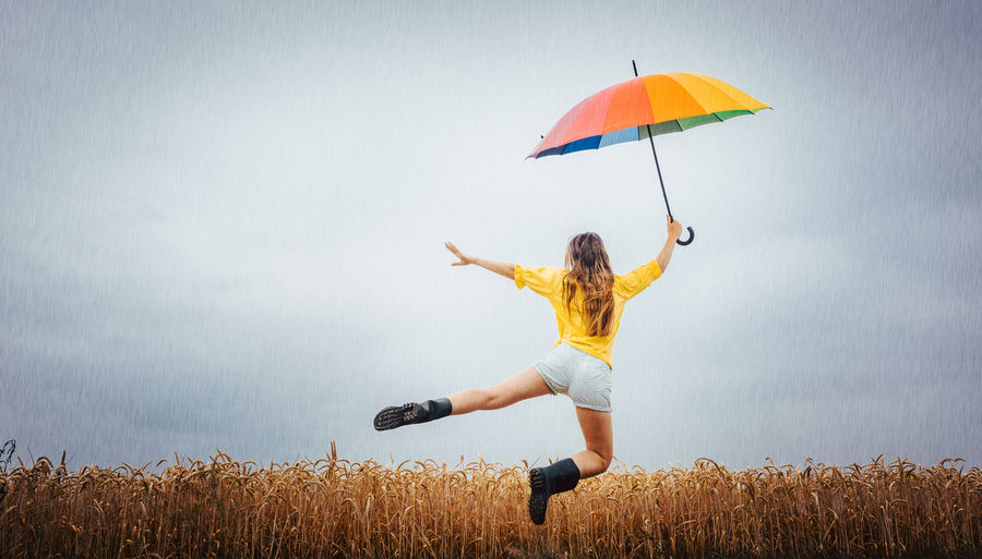 Rear view of woman holding umbrella while levitating against cloudy sky