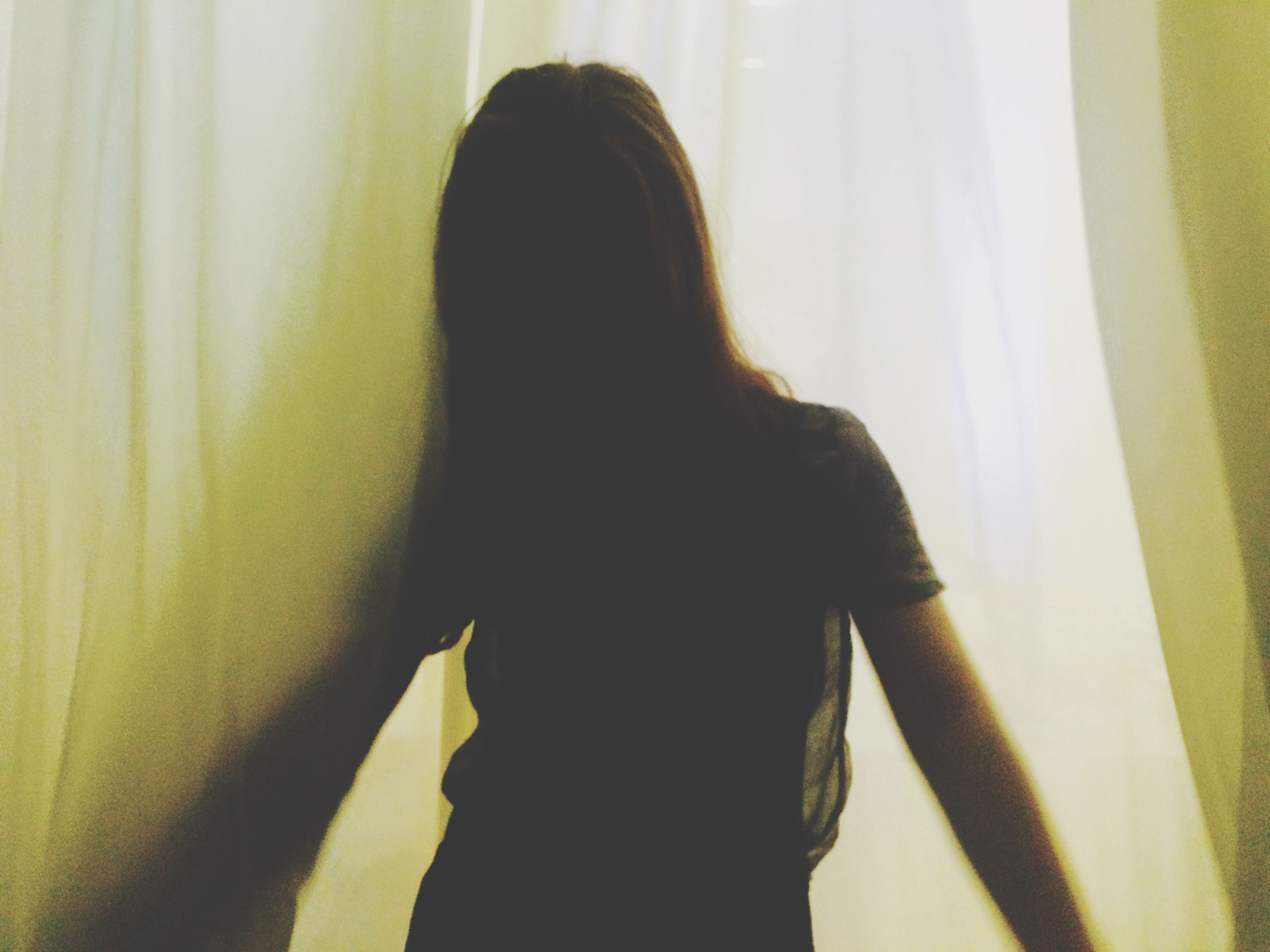 indoors, long hair, lifestyles, young women, young adult, curtain, headshot, leisure activity, person, window, home interior, rear view, standing, contemplation, waist up, wall - building feature, sunlight, casual clothing