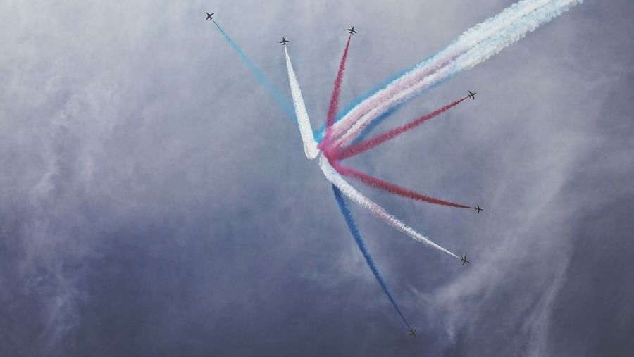 Low Angle View Of Colorful Vapor Trail From Airplanes Against Sky During Airshow