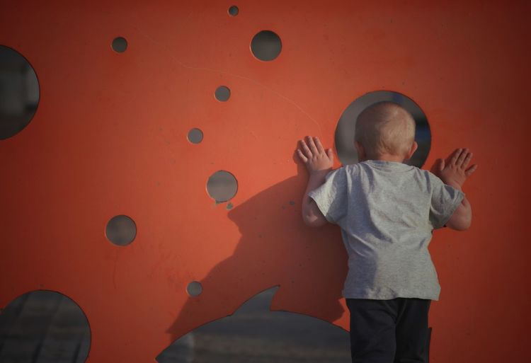Rear view of boy peeking through hole while standing by orange wall
