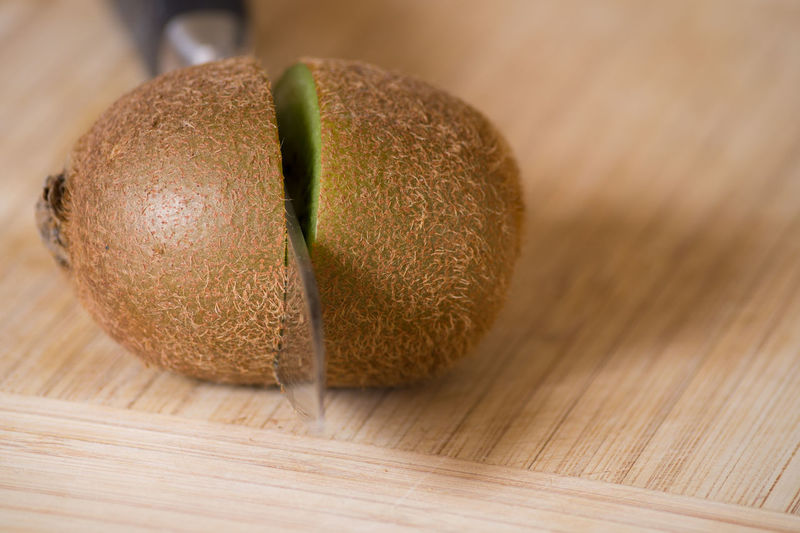 Close-Up Of Sliced Kiwi With Knife On Cutting Board