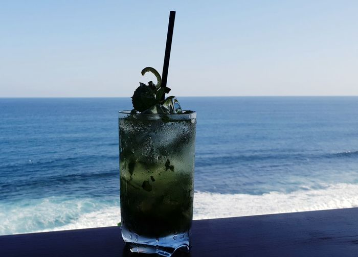View of drink on table against sea