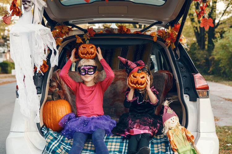 Cute girls wearing costume sitting in car trunk
