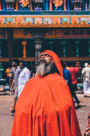 Serious sadhu standing against temple