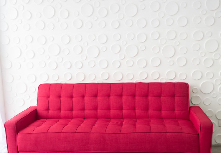 Empty red sofa against wall at home
