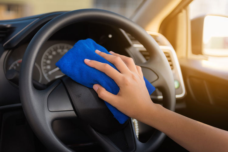 Cropped hand of woman cleaning car steering wheel