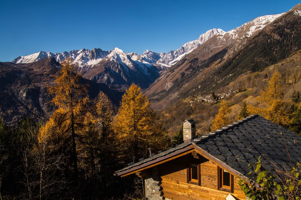 mountain, house, architecture, nature, built structure, mountain range, beauty in nature, building exterior, no people, day, outdoors, snow, tree, scenics, tranquility, cold temperature, clear sky, winter, sky, range