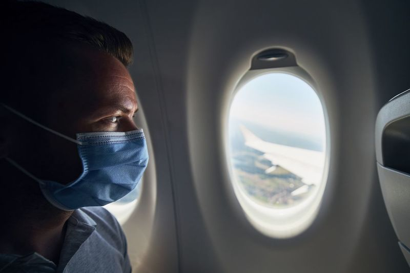 Close-up of man wearing flu mask sitting at airplane