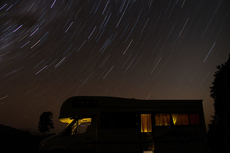 Low Angle View Of Travel Trailer Against Star Trails