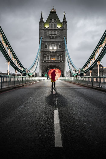 Young woman in yellow raincoat standing on empty tower bridge in london, england