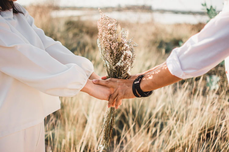 Romantic Beauty In Nature Bride Bridegroom Close-up Day Field Grass Growth Holding Human Body Part Human Hand Leisure Activity Lifestyles Marriage  Men Nature Outdoors People Plant Real People Standing Togetherness Two People Women