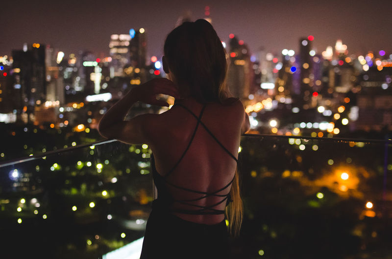 Rear view of woman looking at illuminated cityscape while standing on balcony