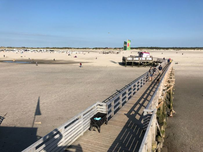High Angle View Of Pier At Beach Against Blue Sky