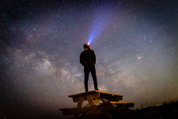 Rear view of man standing against sky at night
